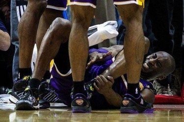 Kobe Bryant holds ankle in pain.