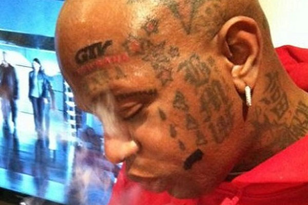 Birdman gets GTV and TRUKFIT logos tatted.