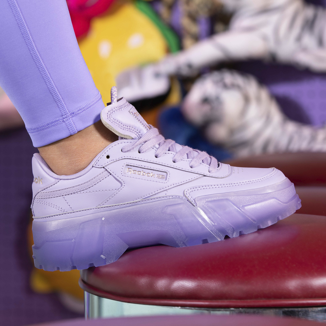 """Reebok has announced its first-ever apparel collection with rap star Cardi B, dubbed """"The Summertime Fine"""" Collection. Set to launch alongside matching footwear colorways of the Cardi B Club C, the drop is coming officially on April 23. A collaborative effort between Reebok and Cardi B, the fabrics and detailing of the apparel collection were thoughtfully curated from the beginning design stages through the entire creation cycle. Having tried on every piece herself, nothing went to production without Cardi's seal of approval. The collection draws inspiration from the 90s, with nods to vintage Reebok apparel and Cardi's distinct memories of summers spent on the Coney Island boardwalk with friends. The range also reflects her bold and transparent personality that influenced the transformation of traditional Reebok silhouettes into a collection sure to be unapologetically in your face. """"I'm so proud to announce my first apparel line with Reebok,' Cardi said on the debut collection. """"This collection gives every woman the product they need to feel sexy and confident; the waist-snatching tights and curve hugging silhouettes make every body look amazing."""" Designed with the female figure in mind, the bold color combinations of pastel purple and bright red are sure to turn heads, while waist-cinching details and contouring cutlines, infused with flirtatious mesh cutouts create that iconic 90s inspired layered look that is totally and completely Cardi B. The colors and materials used in the collection play on day and night monochromatic looks so the versatility of the items can take you straight from the gym to the streets. All apparel will be available in inclusive sizing from 2XS to 4X, bringing this collection to all Cardi fans. The Summertime Fine Collection will be available to purchase alongside matching footwear colorways of the Cardi B Club C , available in women's and kid sizes, at 10am ET April 23 on Reebok.com."""